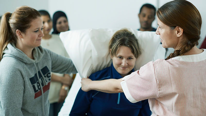 To kvinner står på hver sin side av en pasientseng, hvor en viser hvordan det skal gjøres, og en kvinne spiller pasient
